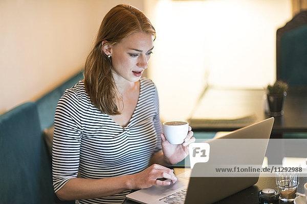Porträt einer Frau  die in einem Café sitzt und einen Laptop benutzt.