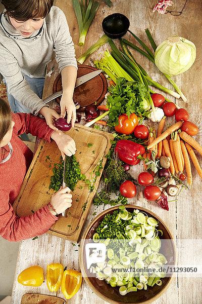 Junge und Mädchen beim Gemüsehacken in der Küche  Draufsicht
