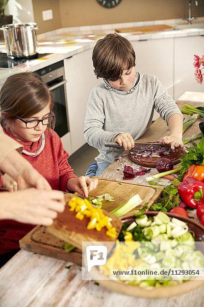 Junge und Mädchen beim Gemüsehacken in der Küche