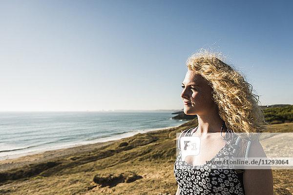 Blond teenage girl enjoying view at seaside