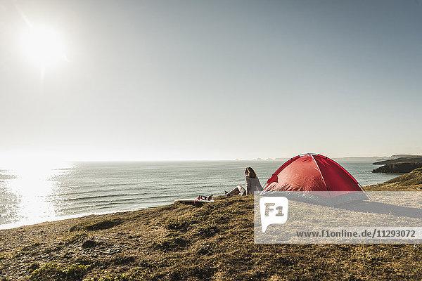 Teenager-Mädchen mit Surfbrett-Camping am Meer