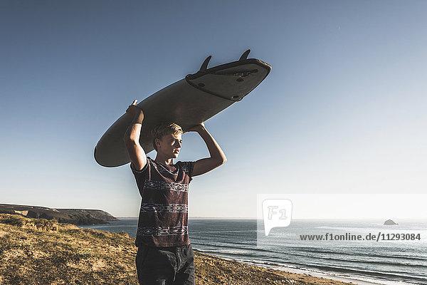 Teenager-Junge mit Surfbrett auf dem Kopf
