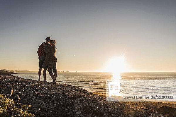 Rückansicht des verliebten jungen Paares bei Sonnenuntergang am Meer