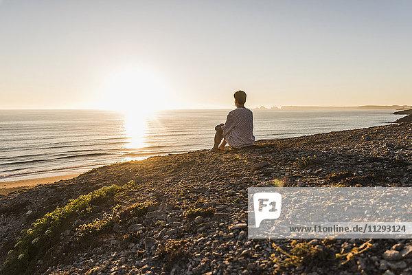 Rückansicht einer Frau  die auf einer Klippe sitzt und den Sonnenuntergang beobachtet.