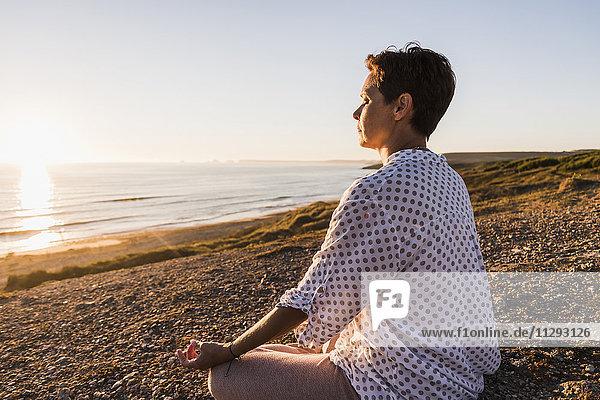 Frau beim Meditieren am Meer bei Sonnenuntergang