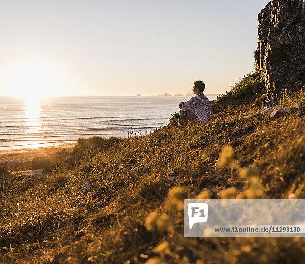 Frau sitzt auf einer Klippe und beobachtet den Sonnenuntergang.
