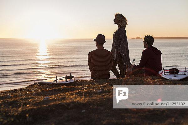 Drei Freunde genießen den Sonnenuntergang am Strand