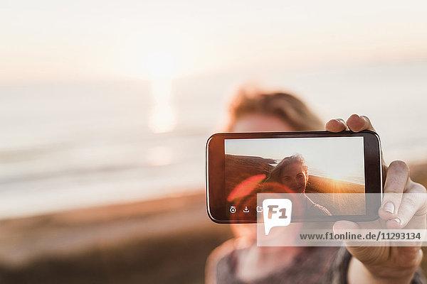 Selfie der lächelnden Teenagerin auf dem Display des Smartphones