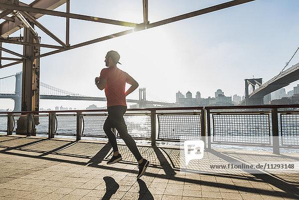 USA  New York City  Mann läuft am East River