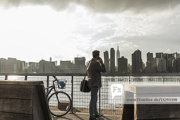 USA  New York City  Geschäftsmann am East River am Handy