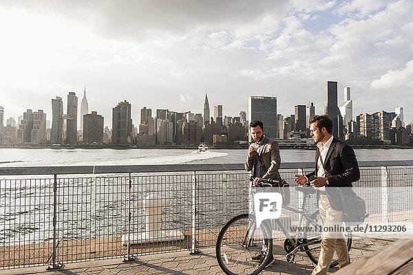 USA  New York City  zwei Geschäftsleute mit Fahrrad entlang des East River