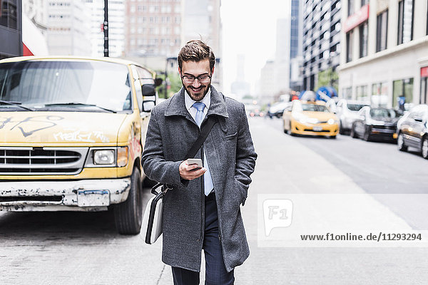 USA  New York City  smiling businessman with cell phone on the go