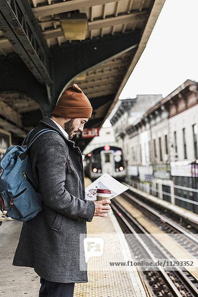 Junger Mann wartet am Bahnsteig der U-Bahn  liest Dokumente