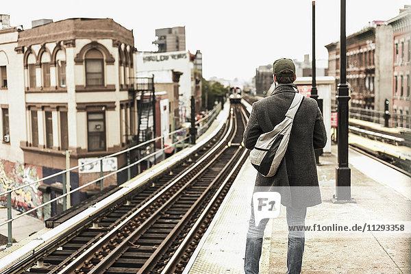 Junger Mann wartet am Bahnsteig auf die U-Bahn