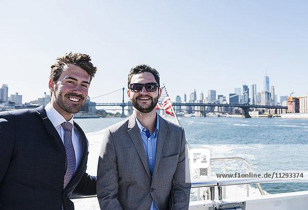 USA  New York City  zwei lächelnde Geschäftsleute auf der Fähre auf dem East River