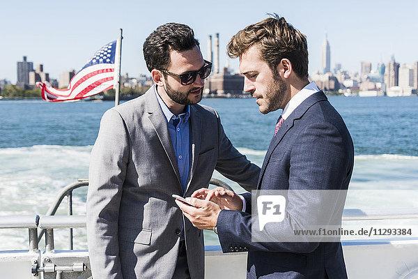 USA  New York City  zwei Geschäftsleute mit Handy auf der Fähre auf East River