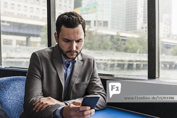 Geschäftsmann auf dem Passagierdeck einer Fähre beim Überprüfen des Handys