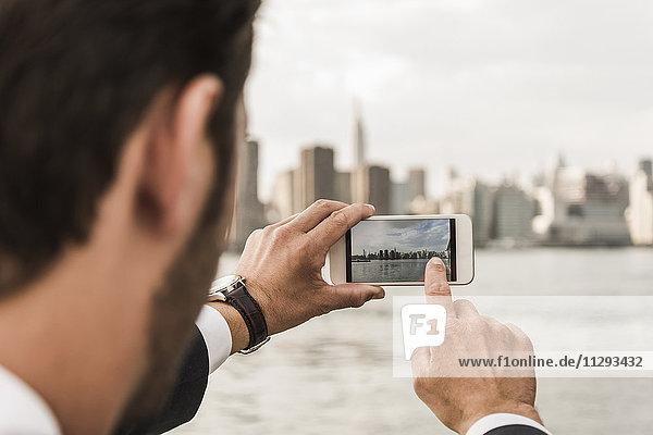 USA  New York City  Mann am East River macht Handyfoto von Manhattan