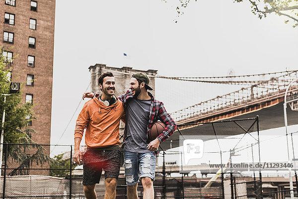 USA  New York  zwei glückliche junge Männer auf einem Outdoor-Basketballplatz