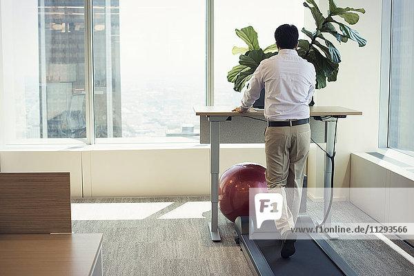 Geschäftsmann-Training auf dem Laufband mit Laptop