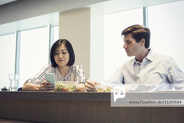 Kollegen im Büro beim gemeinsamen Mittagessen  Frau beim Blick auf Smartphone