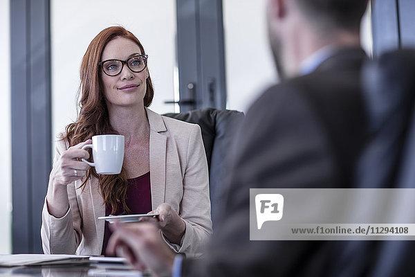 Geschäftsfrau beim Kaffeetrinken bei einem Meeting