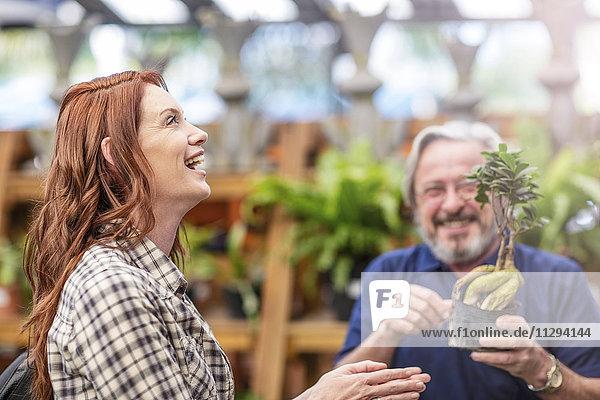 Gärtnerin hilft Frau im Gartencenter