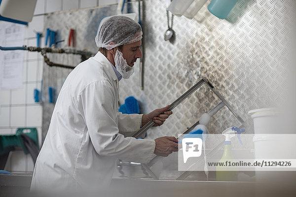 Käsereiarbeiter beim Reinigen von Behälterteilen