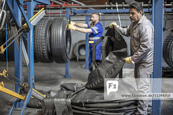 Two tire repairmen working in factory