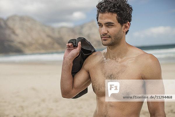 Junger Mann mit Flossen am Strand