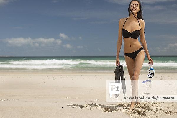 Junge Frau  die mit Schnorchelausrüstung am Strand spazieren geht.
