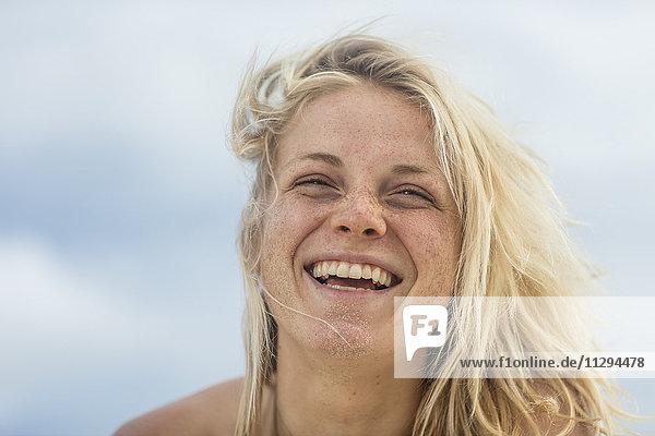Porträt einer glücklichen jungen Frau mit Sand im Gesicht