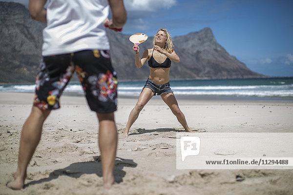 Junges Paar  das Strandpaddel am Strand spielt