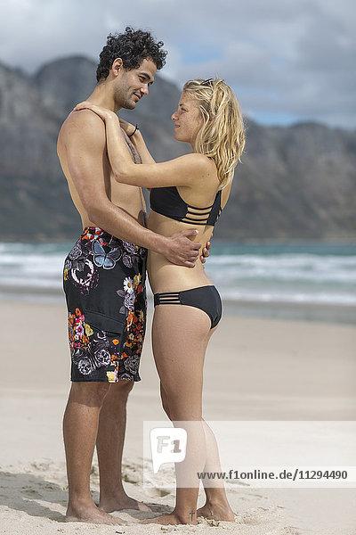 Zartes junges Paar am Strand stehend
