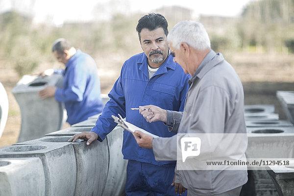 Zwei Männer reden in der industriellen Topffabrik