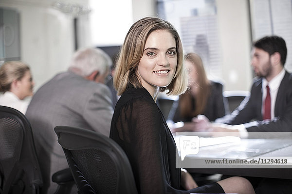 Successful businesswoman sitting in conference  looking at camera