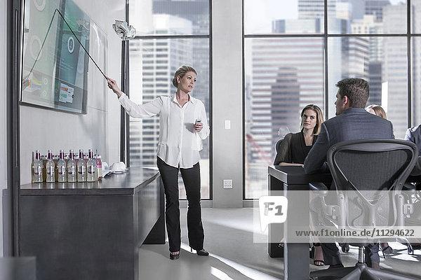 Geschäftsfrau hält Präsentation vor dem Team