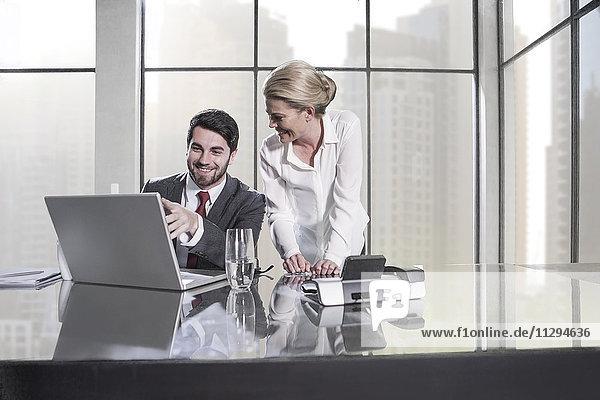 Geschäftsmann und Frau in der Sitzung diskutieren im Büro  mit Laptop