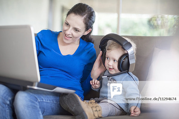 Mother with baby girl wearing headphones using laptop at home