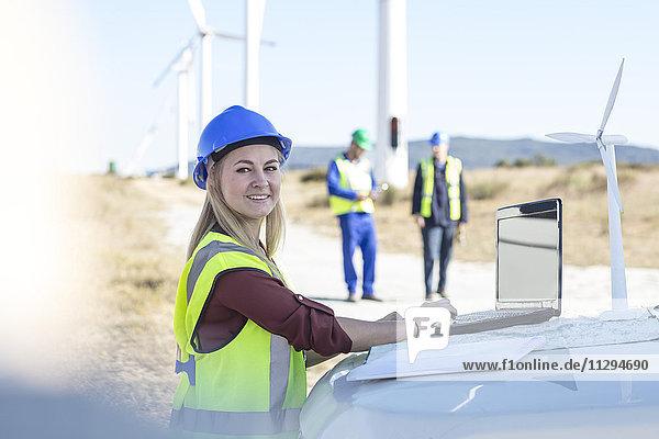 Ingenieurin bei der Arbeit im Windpark  mit Laptop