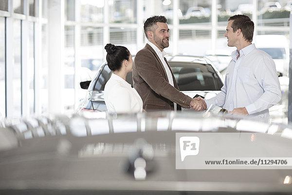 Autohändler schüttelt dem Mann im Autohaus die Hand
