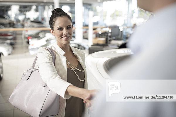 Autohändler schüttelt der Frau im Autohaus die Hand