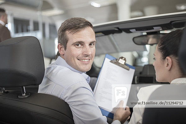 Lächelnder Autohändler mit Klemmbrett und Frau im Auto
