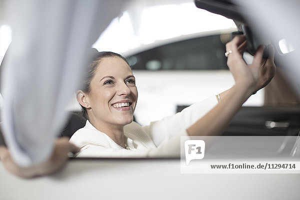 Lächelnde Frau sitzt im Auto beim Autohaus