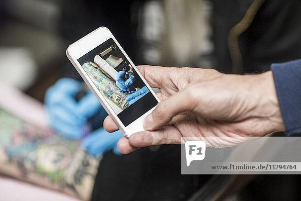 Handy-Bild des Tätowierers bei der Arbeit
