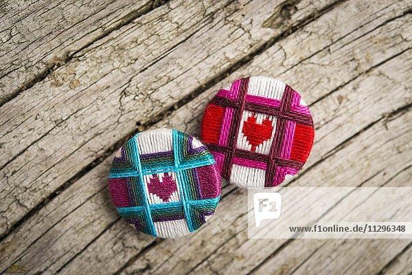 Zwei bunte Posamentenknöpfe  mit Herz als Motiv  auf Holzplatte