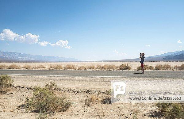 Junger Mann steht auf einer Straße und fotografiert  Highway 190  Landstraße  Death Valley  Death-Valley-Nationalpark  Kalifornien  USA  Nordamerika