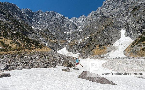Junger Mann springt  Schneefeld vor der Ostwand des Watzmann  Berchtesgadener Land  Oberbayern  Bayern  Deutschland  Europa