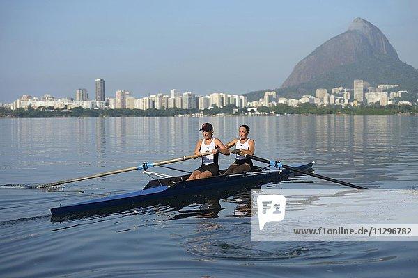 Zwei junge Frauen beim Rudertraining früh Morgens in der Lagune Lagoa Rodrigo de Freitas  Stadtteil Lagoa  hinten Skyline mit Zuckerhut  Rio de Janeiro  Brasilien  Südamerika