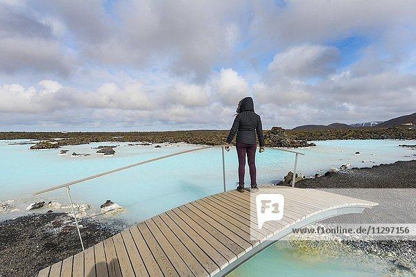 Touristin steht auf einer Holzbrücke  Blaue Lagune bei Grindavik  Südwestisland  Island  Europa